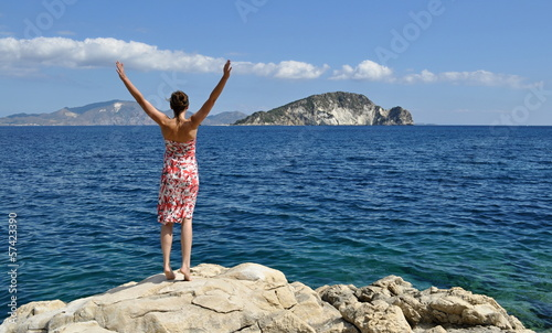 woman with hands up on the coast