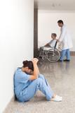 Nurse sitting in the hallway getting depressed