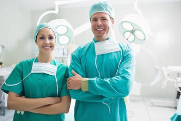 Smiling surgeons looking at camera