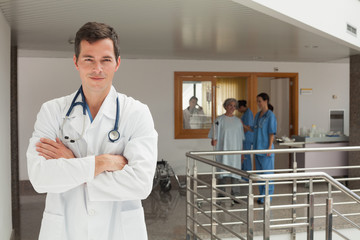 Smiling doctor standing in the hallway