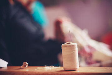 Thread and sewing equipment with woman in background