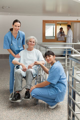 Two nurses with old woman in wheelchair