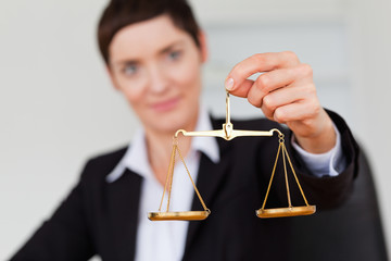 Serious businesswoman holding the justice scale