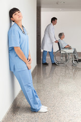 Tired nurse leaning against wall