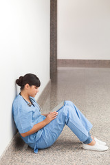 Nurse sitting on the ground looking at file