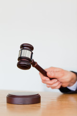 Portrait of a hand knocking a gavel