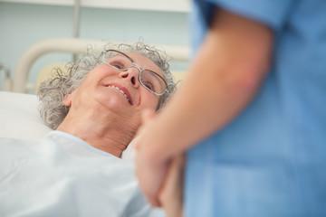Elderly patient looking up at nurse