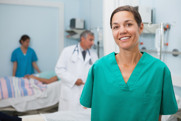 Nurse standing hospital room and smiling
