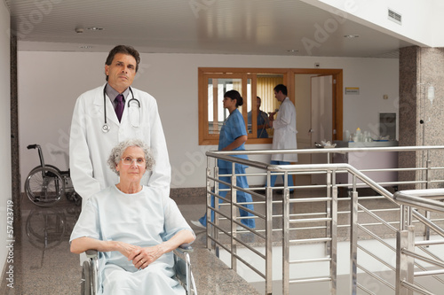 Doctor pushing woman in a wheelchair