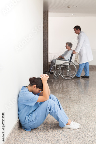 Nurse sitting in the hallway getting depressed