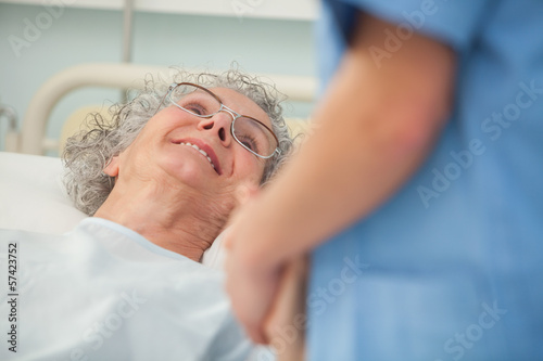 Elderly patient looking up at nurse
