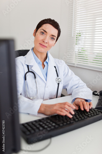 Portrait of a smiling female doctor typing with her computer