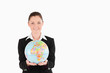 Charming woman in suit holding a globe