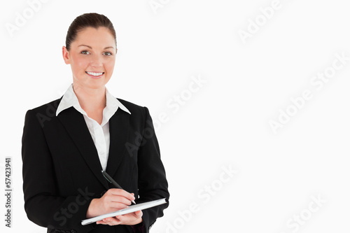 Portrait of a good looking woman in suit writing on a notebook