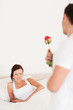 Young woman looking into camera when husband arrives with rose