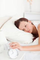 Sleepy red-haired woman lying in bed turning off alarm clock