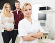 Confident Gynecologist With Expectant Couple In Background