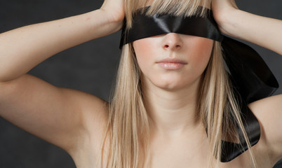 Mysterious beautiful face with ribbon blindfold on eyes