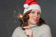 Cute girl in Santa hat holding sparklers