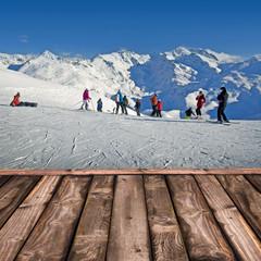 Skieurs sur une piste de ski, terrasse en bois