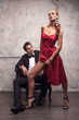 Beautiful girl in red dress trying to seduce handsome man