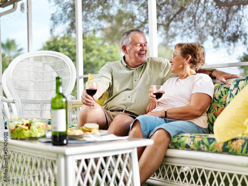 senior couple outside on patio relaxing - 57426302