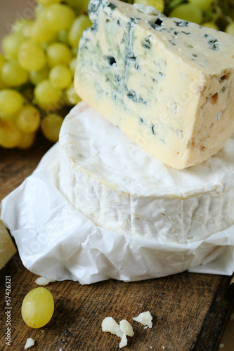 blue cheese and camembert on a background of grape