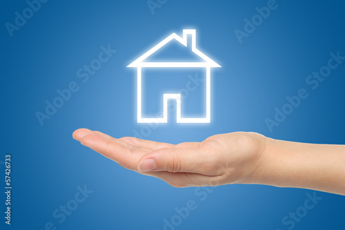 Virtual house with woman hand on blue background .