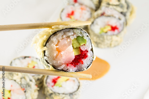 Sushi roll in tempura on white plate and chopsticks
