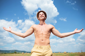 topless man laughing outdoor with arms wide open