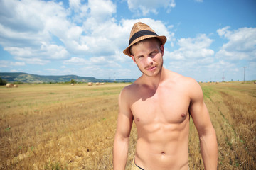 topless man outdoor posing with hat on head