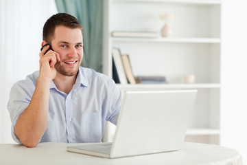 Smiling businessman on the phone in his homeoffice