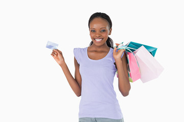 Happy woman with her shopping and credit card on white backgroun