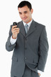 Smiling businessman looking at his cellphone