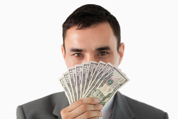 Businessman smelling on banknotes