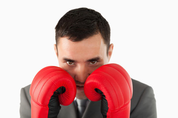 Close up of businessman with boxing gloves taking cover