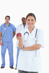 Smiling doctor with apple and colleagues behind her