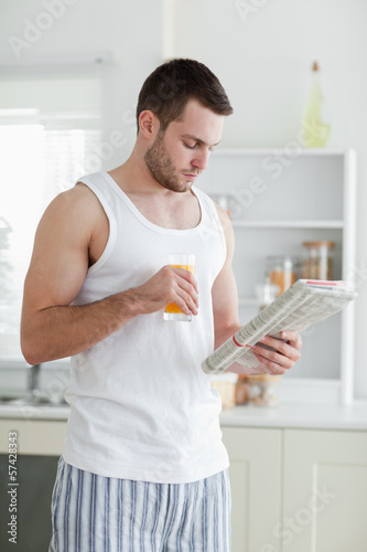 Portrait of a handsome man drinking orange juice while reading t