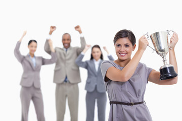 Woman holding up a cup with enthusiastic co-workers