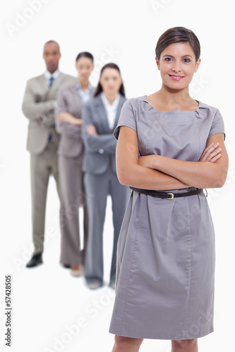 Woman smiling with her business team crossing their arms