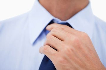 Close up of a hand fixing a tie