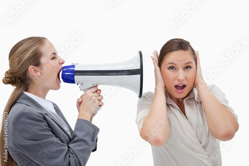 Businesswoman yelling at her coworker through a megaphone
