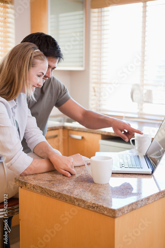 Portrait of a couple having tea while using a laptop