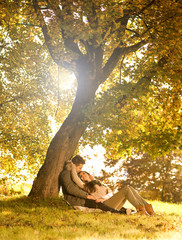 Passionate love in the park under a tree