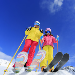 Skiing, skiers, sun and fun - family enyoing winter vacation