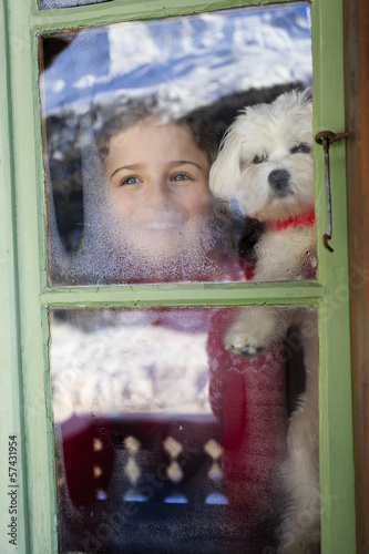 Winter holidays, apres ski - child with puppy  in chalet