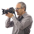 Photographer taking pictures with digital camera on white