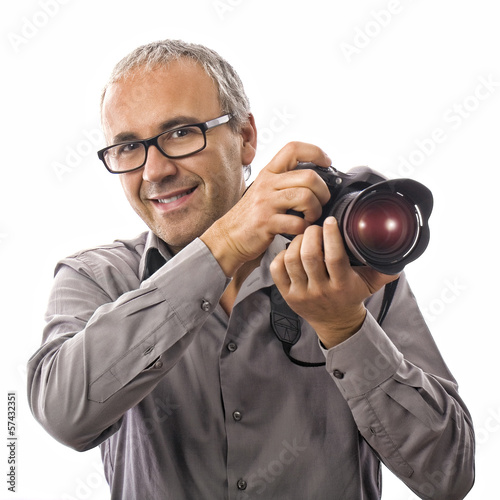 Smiling photographer with professional camera on white