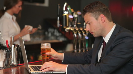 Serious businessman working on his laptop while drinking beer