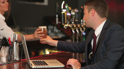 Businessman working on his laptop while having a beer